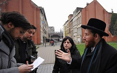 Moshe Friedman, right, talks to journalists with his wife Lea Rosenzweig outside Antwerp's Benoth Jerusalem girls school in Belgium, Jan 7, 2018. (Cnaan Liphshiz/JTA)