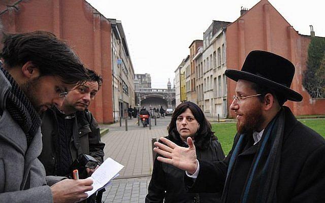 Moshe Friedman, right, talks to journalists with his wife Lea Rosenzweig outside Antwerp's Benoth Jerusalem girls school in Belgium, Jan 7, 2018. (Cnaan Liphshiz/JTA)