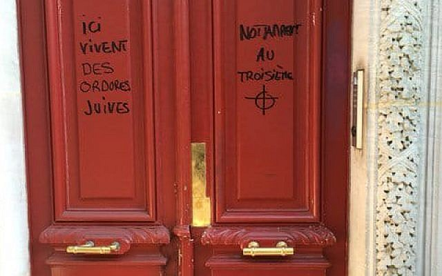 Anti-Semitic graffiti reading 'Jewish scum live here,' on a building in Paris. 'Notably on the third floor,' it adds on the other side of the door, above a drawing of a target. (Twitter)