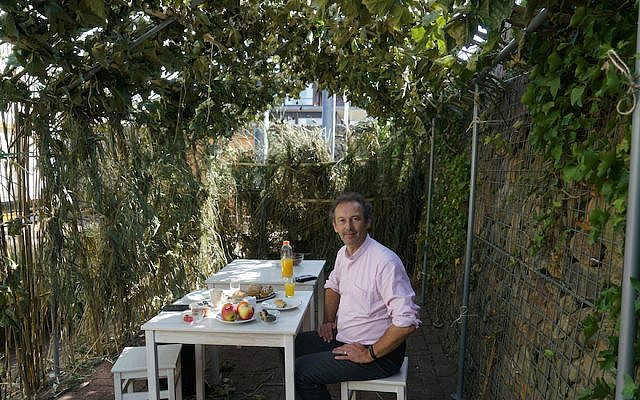 Pastor Piet van Veldhuizen has lunch inside his congregation's sukkah in the Netherlands, September 18, 2018. (Cnaan Liphshiz)