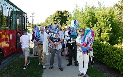 Temple Anshe Hesed congregants carry the Torah scrolls from their old building during a 'de-consecration' event on August 31, 2018. (Alanna Cooper/via JTA)
