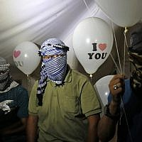 "Masked Palestinians calling themselves the ""night confusion units"" hold incendiary devices attached to balloons to be flown toward Israel, near the border with Israel east of Rafah in the southern Gaza Strip, on September 26, 2018. (AFP Photo/Said Khatib)"