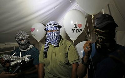 """Illustrative: Masked Palestinians calling themselves the """"night confusion units"""" hold incendiary devices attached to balloons to be flown toward Israel, near the border with Israel east of Rafah in the southern Gaza Strip, on September 26, 2018. (AFP Photo/Said Khatib)"""