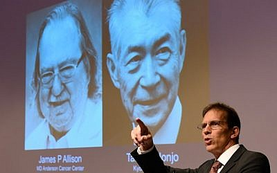 Secretary of the Nobel Committee for Physiology or Medicine, Thomas Perlmann (R) stands next to a screen displaying portraits of James P Allison (L) and Tasuku Honjo during the announcement of the winners of the 2018 Nobel Prize in Physiology or Medicine, during a press conference at the Karolinska Institute in Stockholm, Sweden, on October 1, 2018 (AFP PHOTO / Jonathan NACKSTRAND)