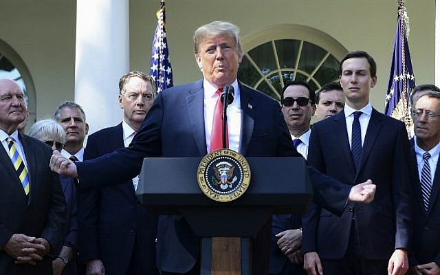 US President Donald Trump surrounded by staff, speaks from the Rose Garden of the White House in Washington, DC, remarking on the United States-Mexico-Canada Agreement on October 1, 2018. (AFP PHOTO / Jim WATSON)