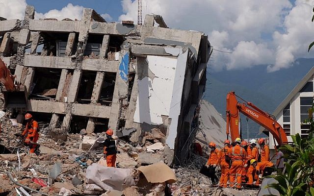 Members of an Indonesian rescue team search for victims from collapsed buildings in Palu in Central Sulawesi, October 2, 2018. (YUSUF WAHIL/AFP)