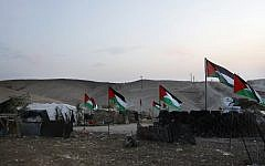 The Palestinian Bedouin village of Khan al-Ahmar, east of Jerusalem in the West Bank, is seen decorated with Palestinian flags on October 2, 2018. (AFP PHOTO / AHMAD GHARABLI)
