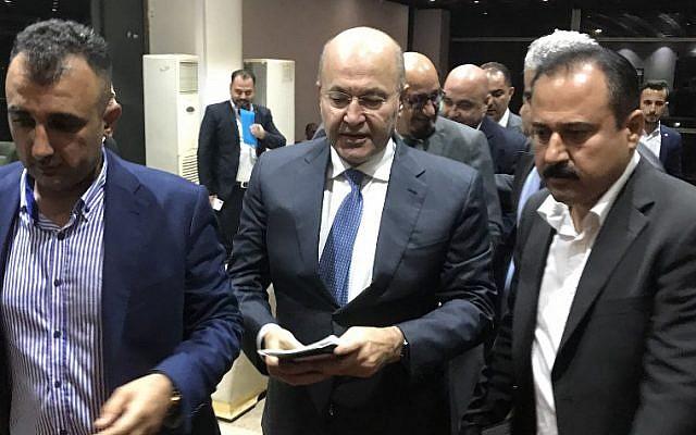 Newly elected Iraqi President Kurdish Barham Saleh (C) walks at the parliament in Baghdad on October 2, 2018.  (AFP PHOTO / Karim AMMAR)
