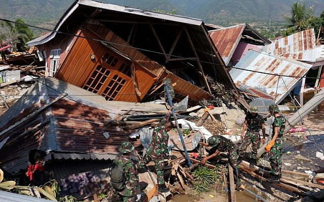 Rescue personnel search for earthquake survivors at a collapsed home in Balaroa, West Palu, Indonesia's Central Sulawesi on October 3, 2018. (YUSUF WAHIL/AFP)