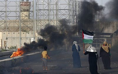 A Palestinian woman holds a flag as protesters demonstrate at the Erez border crossing with Israel in the northern Gaza Strip on October 3, 2018. (AFP/ Said KHATIB)