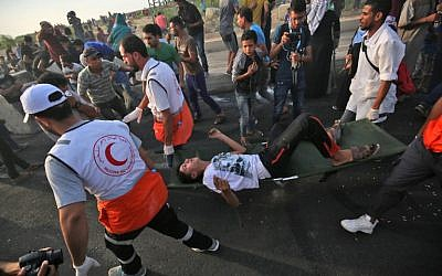 Palestinian paramedics carry an injured man as protesters demonstrate at the Erez border crossing with Israel in the northern Gaza Strip on October 3, 2018. (AFP/Said Khatib)