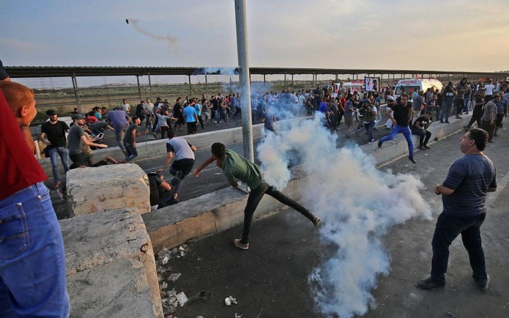 A Palestinian protester throws back a tear gas canister as people demonstrate at the Erez border crossing with Israel in the northern Gaza Strip on October 3, 2018. (AFP / SAID KHATIB)