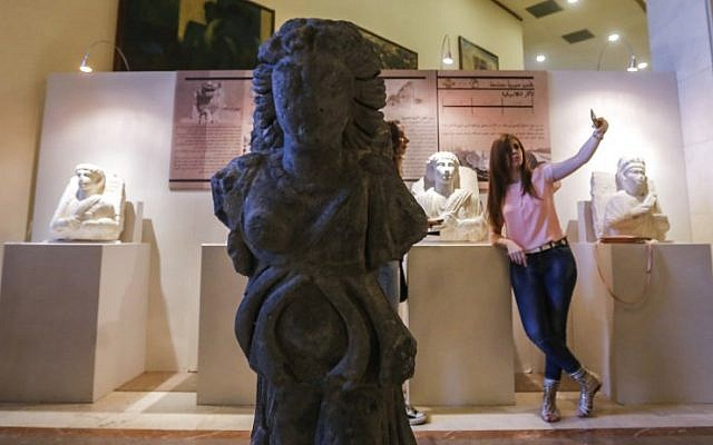 """A Syrian woman takes a photograph of herself with her phone next to artifacts recovered by the government from archaeological sites affected by fighting across the country, on display at an exhibition titled """"Syria's Recovered Treasures"""" at the Dar Al-Assad for Cutlure and Arts in the capital Damascus on October 3, 2018. (AFP Photo/Louai Beshara)"""