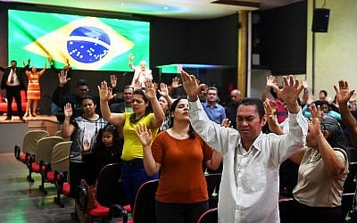 FILE -- In this photo taken on September 21, 2018 faithful pray at an evangelical church in Brasilia for the recovery of Brazilian right-wing presidential candidate Jair Bolsonaro, who suffered a knife attack during a campaign rally (AFP PHOTO / EVARISTO SA)