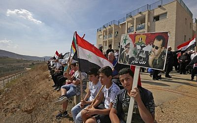 Members of the Druze community sit holding portraits of Syrian President Bashar Assad and Syrian national flags during a rally in the Druze village of Majdal Shams in the Israeli-annexed Golan Heights on October 6, 2018 commemorating the 45th anniversary of the 1973 Arab-Israeli war (AFP PHOTO / JALAA MAREY)