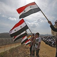 Young members of the Druze community wave Syrian flags during a rally in the Druze village of Majdal Shams in the Golan Heights on October 6, 2018, commemorating the 45th anniversary of the 1973 Arab-Israeli war (AFP Photo/Jalaa Marey)