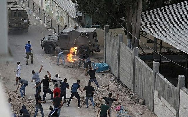 Palestinians throw stones and molotov cocktails at Israeli forces in the West Bank village of Shuweika on October 7, 2018. (AFP Photo/Jaafar Ashtiyeh)