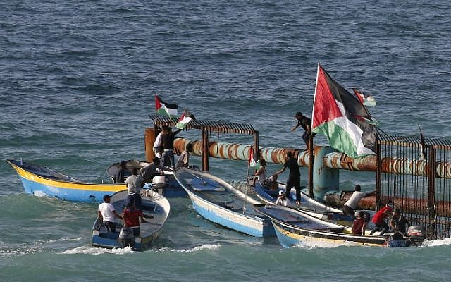 Palestinian protestors in boats place their national flag on a metal structure at the maritime border with Israel, in the northern Gaza Strip, on October 8, 2018. (AFP PHOTO / Said KHATIB)
