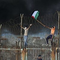 Palestinian protestors place their national flag on a metal structure during a demonstration on the beach near the maritime border with Israel, in the northern Gaza Strip, on October 8, 2018. ( Said KHATIB / AFP)
