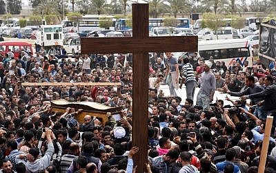 In this file photo taken at a funeral procession at the Monastery of Marmina in the city of Borg El-Arab, east of Alexandria, Egypt, on April 10, 2017, mourners carry a large cross and the coffin of one of the victims of the blast at the Coptic Christian Saint Mark's church in Alexandria the previous day. (Mohamed El-Shahed/AFP)