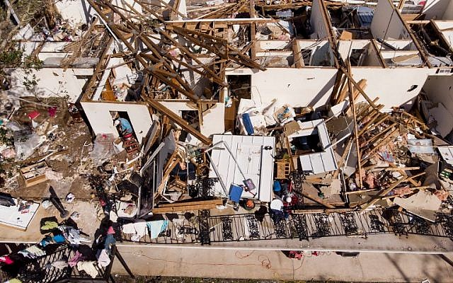 A man works though the remains of an apartment in the aftermath of Hurricane Michael October 11, 2018 in Panama City, Florida. (Photo by Brendan Smialowski / AFP)