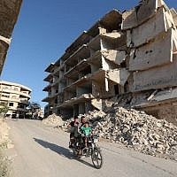 In this file photo taken on September 27, 2018 shows Syrian men riding a motorcycle past heavily-damaged buildings in the rebel-held town of Maaret al-Numan, in the north of Idlib province. (OMAR HAJ KADOUR / AFP)