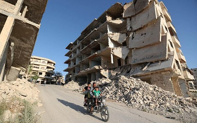 In this file photo taken on September 27, 2018, Syrian men ride a motorcycle past heavily-damaged buildings in the rebel-held town of Maaret al-Numan, in the north of Idlib province. (Omar Haj Kadour/AFP)