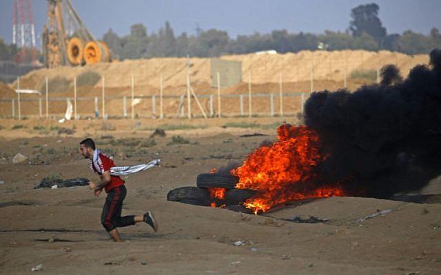 A Palestinian protester runs by burning tires at the Israel-Gaza border, east of Gaza city, on October 12, 2018. (Said KHATIB / AFP)