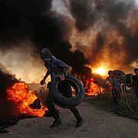 Palestinian protesters carry tires as smoke billows at the Israel-Gaza border, east of Gaza city, on October 12, 2018. (SAID KHATIB / AFP)