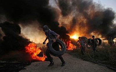 Palestinian protesters carry tires as smoke billows at the Israel-Gaza border, east of Gaza city, on October 12, 2018. (SAID KHATIB / AFP)