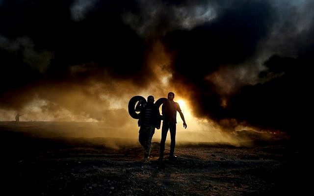 Palestinian protesters carry tires as smoke billows from burning tires at the Israel-Gaza border, east of Gaza city, on October 12, 2018 (Photo by SAID KHATIB / AFP)