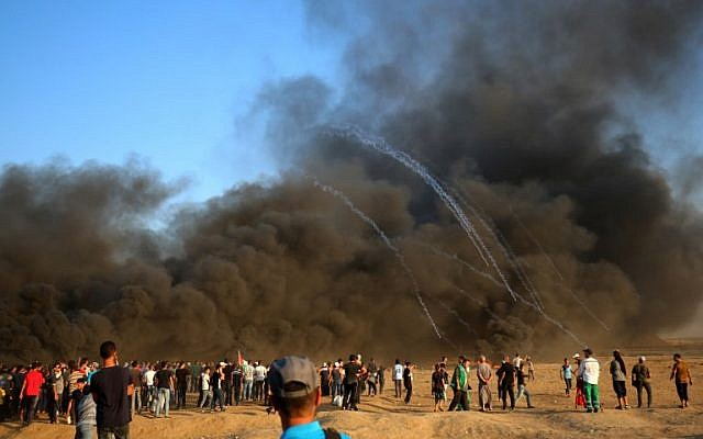 Palestinian protesters gather in the smoke billowing from burning tyres as Israeli forces launch tear gas canisters at the Israel-Gaza border, east of Gaza city, on October 12, 2018. (Photo by SAID KHATIB / AFP)