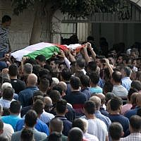 Palestinian carry the body of 48-year-old mother of eight, Aisha Rabi, who died of her wounds after the car she was travelling in with her husband was hit by stones, during her funeral in the West Bank village of Biddya, on October 13, 2018. (JAAFAR ASHTIYEH / AFP)