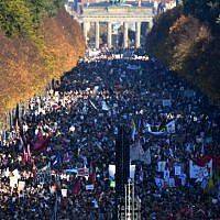 """Demonstrators gather in Berlin's Tiergarten district between the Brandenburg Gate and the Victory Column during a major demonstration for an open and caring society organized by the action group """"Unteilbar"""" (indivisible) on October 13, 2018. (John MACDOUGALL / AFP)"""