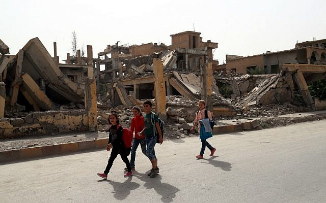 School children walk past destroyed buildings in the northern Syrian city of Raqqa on October 14, 2018. (Delil Souleiman/AFP)