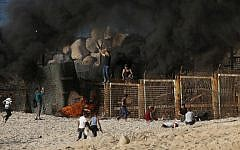 Palestinian protesters climb a fence separating them from Israeli security forces during demonstration on the beach near the maritime border with Israel, in the northern Gaza Strip, on October 15, 2018. (Said KHATIB / AFP)