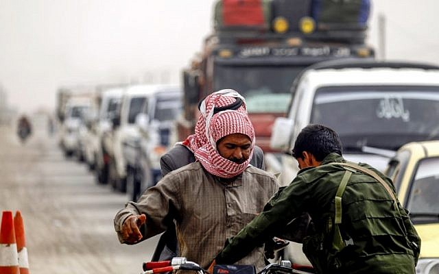 A member of the Raqqa civil council's local security forces inspects a motorcycle and its riders at a checkpoint securing vehicles entering into the eastern Syrian city and former Islamic State (IS) stronghold, on October 16, 2018. (Delil Souleiman/AFP)