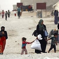 Displaced Syrians, from the eastern city of Deir Ezzor and Raqqa who were forced to leave by the war against the Islamic State group, are pictured walking around at the Ain Issa camp on October 17, 2018. (Delil souleiman / AFP)
