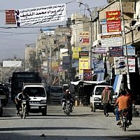 Banners advertising shops and clinics are pictured hanging in a street in the Syrian city of Raqqa on October 18, 2018. (Delil Souleiman/AFP)
