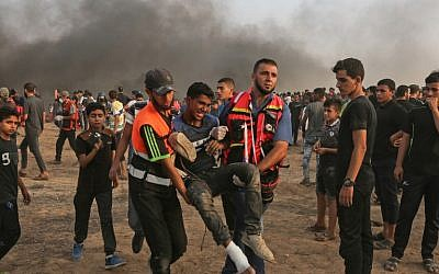 Palestinian paramedics carry an injured protester during a demonstration near the border with Israel, east of Gaza City, on October 19, 2018. (Photo by MAHMUD HAMS / AFP)