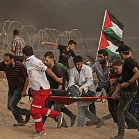 Palestinian paramedics carry an injured protester during a demonstration near the border with Israel, east of Gaza City, on October 19, 2018. (Mahmud Hams/AFP)