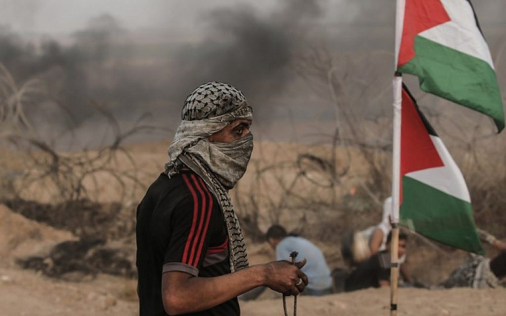 A Palestinian protester stands by his national flag during a demonstration near the border with Israel, east of Gaza City, on October 19, 2018. (MAHMUD HAMS / AFP)