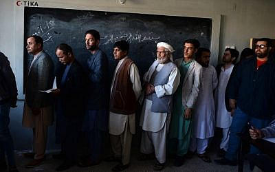 Afghan men line up to cast their vote at a polling centre for the country's legislative election in Mazar-i-Sharif on October 20, 2018. (FARSHAD USYAN / AFP)