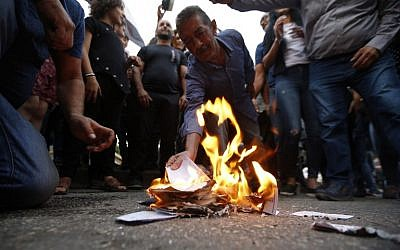 Druze residents of Majdal Shams in the Golan Heights set ablaze makeshift ballot papers during a protest on October 19, 2018. (Jalaa Marey/AFP)