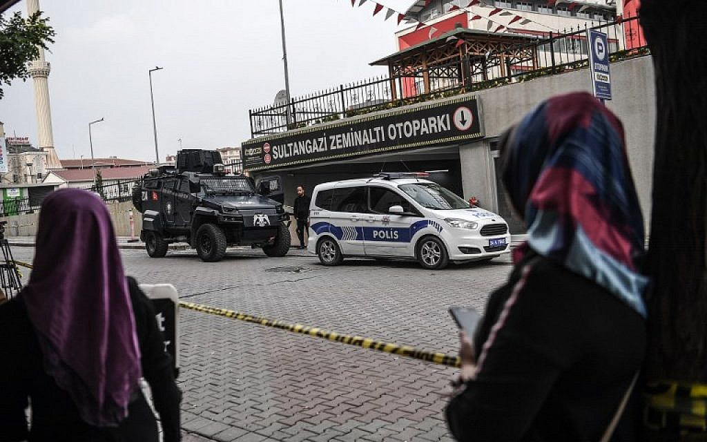 Women look as Turkish police stand guard as they cordoned off an underground car park, on October 23, 2018 in Istanbul, where an abandoned car belonging to the Saudi consulate has been found, three weeks after the murder of journalist Jamal Khashoggi in the Saudi consulate. (OZAN KOSE / AFP)
