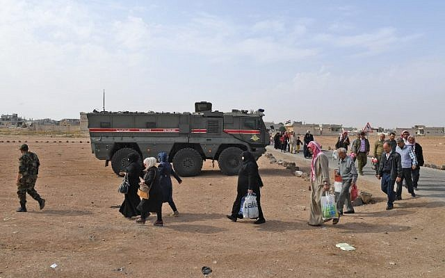 Syrian families walk as members of Russian and Syrian forces stand guard at the Abu Duhur crossing on the eastern edge of Syria's Idlib province on October 23, 2018.(GEORGE OURFALIAN / AFP)