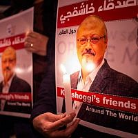People hold posters picturing Saudi journalist Jamal Khashoggi and lightened candles during a gathering outside the Saudi Arabia consulate in Istanbul, on October 25, 2018. (Yasin Akgul/AFP)