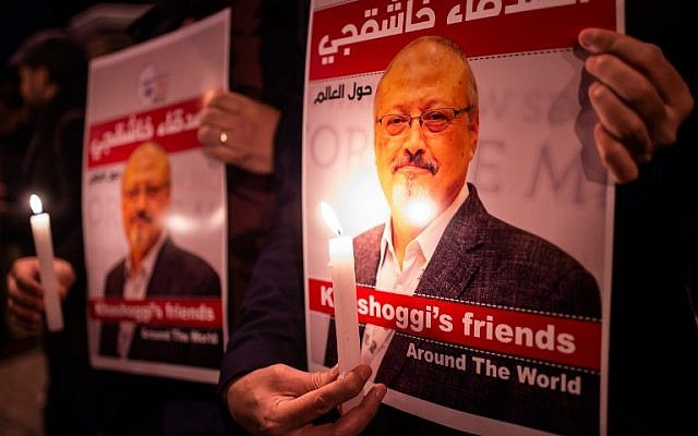 People hold posters picturing Saudi journalist Jamal Khashoggi and candles during a gathering outside the Saudi Arabia consulate in Istanbul, on October 25, 2018. (Yasin Akgul/AFP)