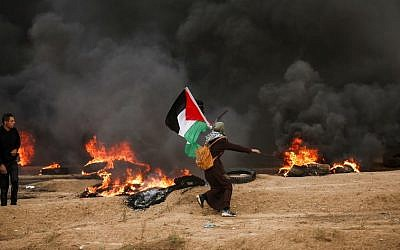A Palestinian woman runs with a Palestinian flag, amid black smoke from tires burned by protesters, during clashes following a riot near the border with Israel east of Gaza City on October 26, 2018. (Photo by MAHMUD HAMS / AFP)