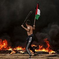 A Palestinian holds a Palestinian flag as he uses a slingshot to hurl rocks at Israeli troops during clashes near the border with Israel, east of Gaza City, on October 26, 2018. (Mahmud Hams/AFP)